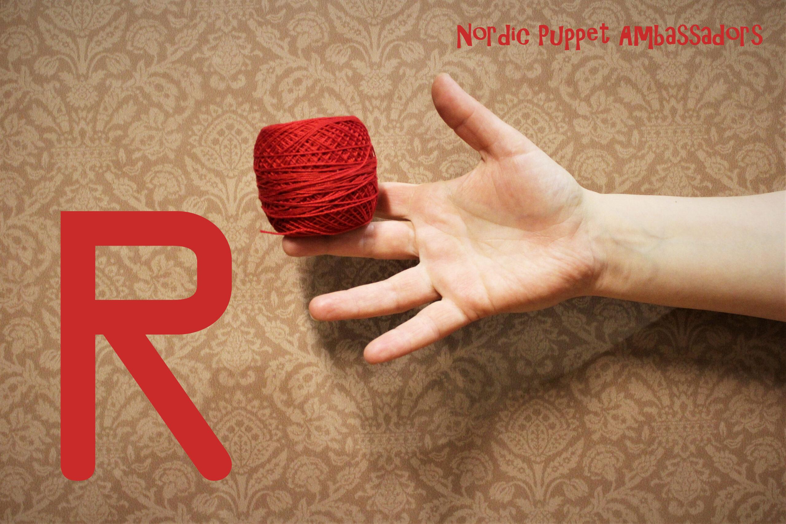 Esityksen kuva: lankakerä kädessä ja R-kirjain